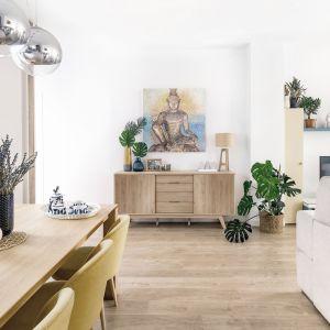 Dekory imitujące drewno Jackson Hikory (stół i szafka) oraz Jesion Górski (szafka) doskonale łączą się z zielonymi roślinami - tymi żywymi i na obrazkach. Fot. Pfleiderer