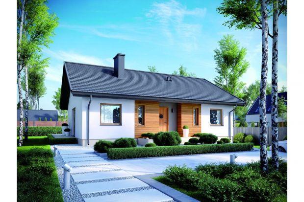 Prostokątna bryła przykryta dwuspadowym dachem prezentuje się stylowo i efektownie, a do tego sprzyja ograniczeniu kosztów budowy. Modny charakter domu podkreślają szerokie przeszklenia oraz elewacja utrzymana w chłodnej bieli, przełamana jednak c