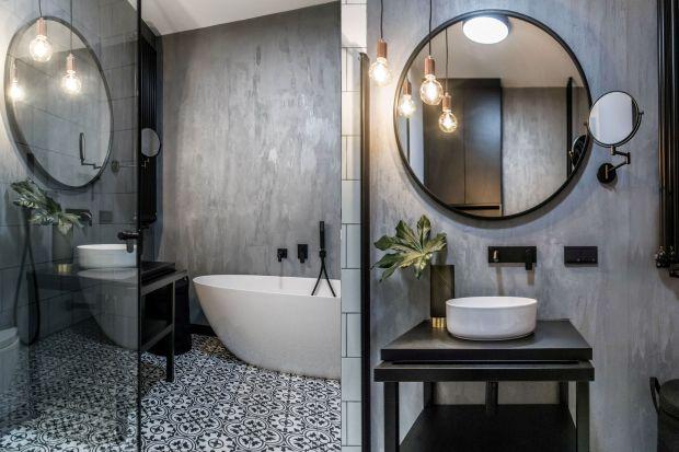 Surowa, ale niepozbawiona przytulności łazienka zrobiona zostało na szaro. Nie brak tu także czarnych detali aranżacyjnych o industrialnym charakterze. To świadomy zwrot ku loftowym wzorcom, które ciągle przeżywają swój renesans w urządzaniu w