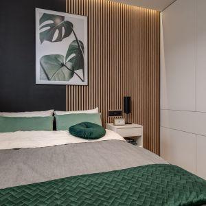 Czerń i drewniane panele na ścianie za łóżkiem to doskonałe połączenie. Obraz z elementami zieleni pięknie dopełnił całość. Projekt: Dorota Pilor. Fot. Radosław Sobik