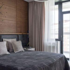 Drewno na ścianie daje sypialni przytulnego charakteru. Projekt: Design Studio Geometrium. Fot. E. Kulibaba