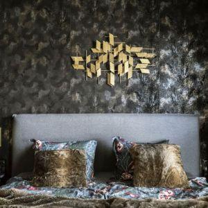 Pierwszoplanowym bohaterem w tej sypialni jest ściana za łóżkiem. Biel, szarość, czerń przypomina nocne wzburzone morze, a na nim żeglarz na złotym statku. Projekt: Magdalena Młynarska. Fot. Yassen Hristov/Hompics.com