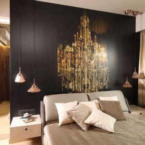 Ścianę pomalowaną na czarny kolor zdobi złota fototapeta, która doskonale koresponduje z dekoracyjnymi lampami w tym samym kolorze. Projekt: Laura Sulzik. Fot. Bartosz Jarosz