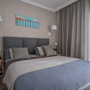 Ścianę za łóżkiem zdobi tapeta z delikatnym wzorem. Projekt: Jacek Tryc. Fot. Jacek Tryc - wnętrza