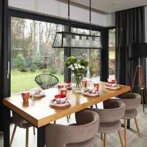 Duży, drewniany stół organizuje strefę jadalnianą, budując przy tym ciepłą i przytulna atmosferę we wnętrzu.