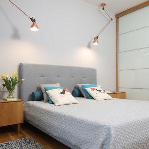 Głównym, choć nie jedynym elementem wystroju sypialni jest tapicerowane łoże w szarym stonowanym odcieniu.