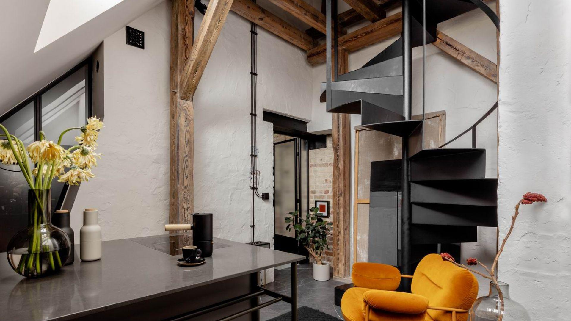 Na antresoli urządzona została druga sypialnia z otwartą łazienką, do których prowadzą kręcone schody. Projekt: Przemek Maziarz. Fot. Ola Dermont