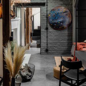 Dzięki różnicy wysokości poddasza projektanci mogli wprowadzić do wnętrza różne oprawy oświetleniowe, tworzące niezwykłe kompozycje świetlne na ścianach oraz posadzkach.  Projekt: Przemek Maziarz. Fot. Ola Dermont
