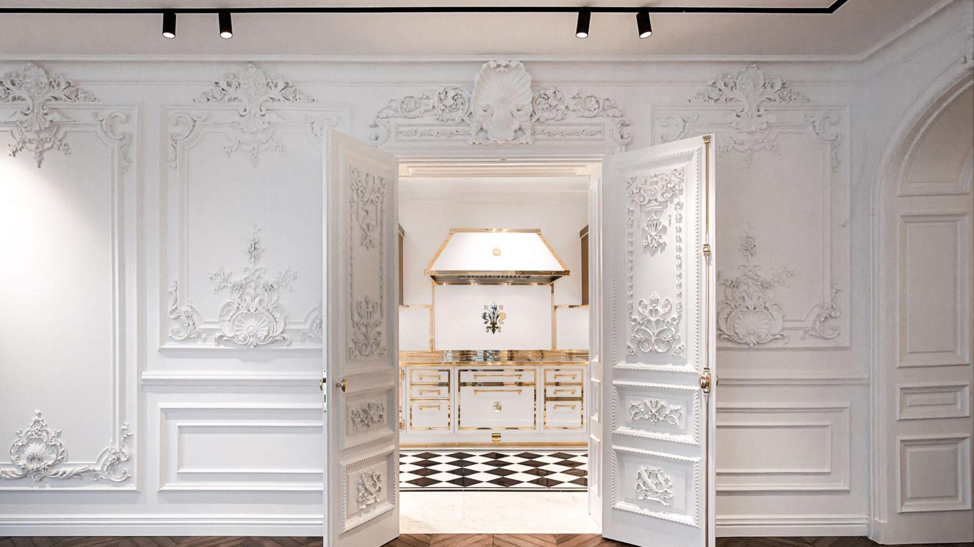Projekt kuchni z meblami w bieli i polerowanym mosiądzu. Fot. Officine Gullo