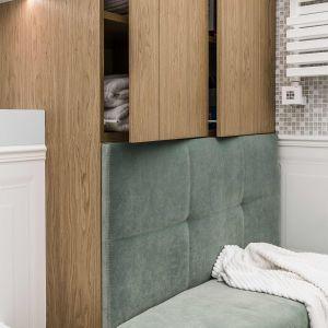 Stylizowane siedzisko w kolorze mięty w drewnianej zabudowie prezentuje się niezwykle efektownie. Projekt Pracownia Magma. Fot. Fotomohito