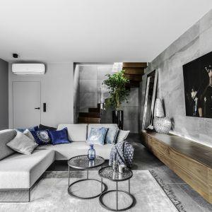 W nowoczesnym salonie podłogę i ścianę za telewizorem zdobią szare płytki imitujące beton. Projekt Agnieszka Morawiec. Fot. Dekorialove