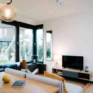 Duże okna w przestrzeni dziennej sprawiają, że wnętrze jest jasne. Projekt: Barbara Bulska, Piotr Czajkowski, pracownia PLAN A. Fot. Adam Biermat