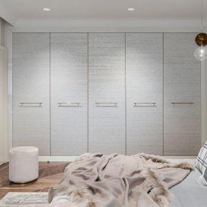 Praktyczna zabudowa garderobiana subtelnie wpisuje się w wystrój pomieszczenia. Projekt Joanna Safranow. Foto. Fotomohito