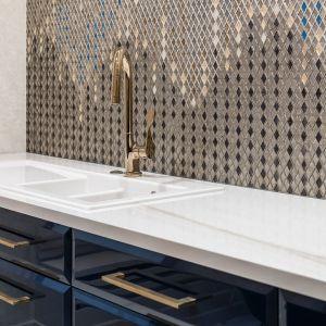 Mozaika pokrywa całą ścianę kuchni przypominając roziskrzoną taflę oceanu, w której odbijają się promienie słońca. Projekt Joanna Safranow. Foto. Fotomohito