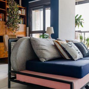 Sofa z metalowym rusztowaniem, w kolorach nawiązujących do lat 90. Poduszki ze wzorem Fornasetto. Czarno-biały dywan. Dom FM, projekt: Mombá Architektura (Argentyna). Zdjęcia: Felipe Lopez