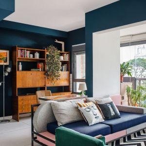 Sofa zaprojektowana na zamówienie przez architektów. W podobnym stylu Sona od Noti od 2.140 zł. Regał w stylu vintage, dywan Zarif Tapetes.  Dom FM, projekt: Mombá Architektura (Argentyna). Zdjęcia: Felipe Lopez