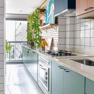 w kuchni zastosowano dwukolorową zabudowę meblową Na dole - miętowa matowa zieleń, na górze - naturalne drewno. Dom FM, projekt: Mombá Architektura (Argentyna). Zdjęcia: Felipe Lopez