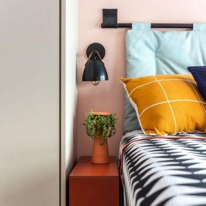 Łóżko z tapicerowanym zagłówkiem, który przymocowane do czarnego stalowego rusztowania. Czarna lampka ścienna idealna do sypialni. Dom FM, projekt: Mombá Architektura (Argentyna). Zdjęcia: Felipe Lopez