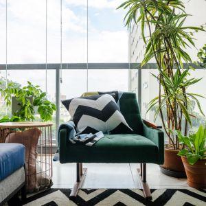 Tapicerowany fotel vintage w butelkowej zieleni zestawiono z piękną naturalną roślinnością. Dom FM, projekt: Mombá Architektura (Argentyna). Zdjęcia: Felipe Lopez