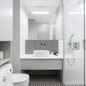 Łazienkę urządzoną w bieli pięknie ożywia czarno-biała mozaika zastosowana w strefie umywalki. Projekt: Anna Maria Sokołowska. Fot. Fotomohito