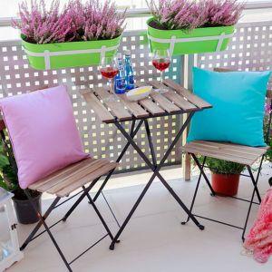 Ten balkon jest niewielki. Udało się tu jednak zmieścić nieduży stolik i krzesła. Całość aranżacja dopełniły bardzo ładnie skomponowane kolorowe dodatki oraz kwiaty. Projekt: Agnieszka Romańczyk (ArchDesign). Fot. Adam Kocimski