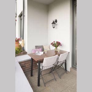 Drewniany blat stolika pasuje do białych krzeseł oraz ścian, zaś czarne nogi do wiszącej lampy. Projekt: Joanna Morkowska-Saj, Saje Architekci. Fot. Foto&Mohito