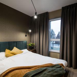 Ciemna kolorystyka zastosowana w sypialni nadaje jej przytulności. Brązy idealnie pasują do butelkowej zieleni. Pracownia KODO Projekty i Realizacje