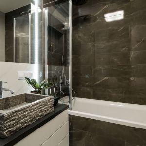 W łazience zdecydowano się na rozwiązanie 2 w 1, a więc wannę z opcją prysznica. To rozwiązanie doskonale sprawdza się w małych wnętrzach. Pracownia KODO Projekty i Realizacje