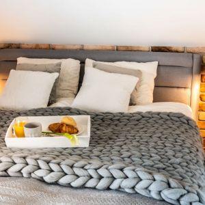 Szare tapicerowane łóżko z niskim zagłówkiem. Urody dodaje mu gruby pled z czesankowej wełny - ok. 300 zł, np. Stiulove.pl. Projekt Małgorzata Szpak. Fot. Lukas Patecki