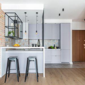 Minimalistyczną kuchnię urządzono w matowych szarościach. Ceglana ściana i stalowe, malowane proszkowa czarne półki nawiązują do stylistyki loftów. Projekt Decoroom. Fot. Pion Poziom