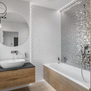 Przestrzenne wzory płytek dodają dynamiki aranżacji łazienki. Nad umywalką pięknie prezentuje się okrągłe lustru.  Projekt: Estera i Robert Sosnowscy. Fot. FotoMohito
