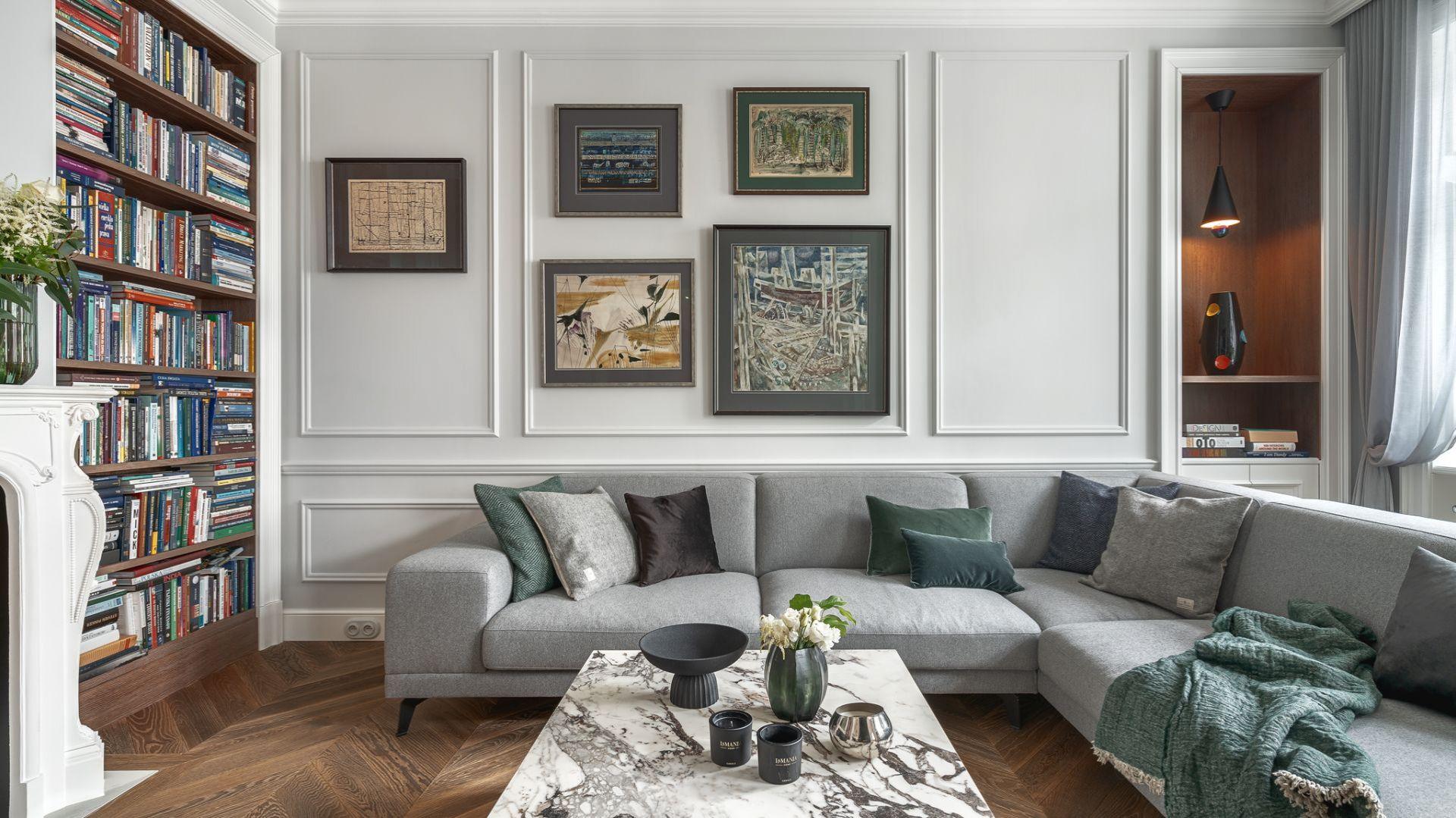 Jasnoszara kanapa świetnie wygląda także w klasycznym wnętrzu, tu akurat na tle sztukaterii. Kanapa Nobonobo, projekt by Whitecastle.pl, fot.  Tom Kurek