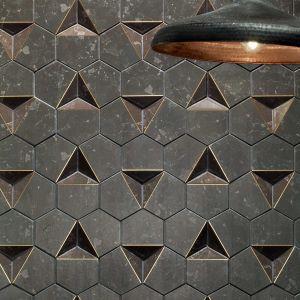Motyw sześcioboku widoczny jest także w kolekcji Scoria, projektu Macieja Zienia, gdzie został przedstawiony w niezwykle oryginalny sposób. W skład kolekcji wchodzą mozaiki w trzech wariantach kolorystycznych: ciemnoszarym, kamiennym (Scoria Black), niejednorodnej bieli (Scoria White) oraz z dodatkiem złotych zdobień (Scoria Black 1). Połączenie heksagonów pozwoliło uzyskać nowy, trójwymiarowy kształt żłobień w płytce, z wyraźnie wyodrębnionym wklęsłym i wypukłym. Scoria - 29,89 zł/szt.