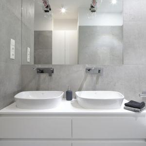 W tej nowoczesnej łazience postawiono na szarości. To one nadają on całej aranżacji i doskonale pasują do białych umywalek oraz szafki. Projekt: Katarzyna Mikulska-Sękalska. Fot. Bartosz Jarosz