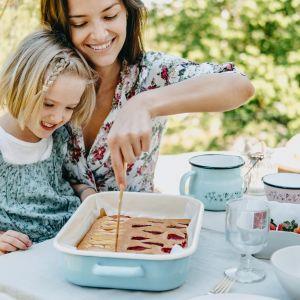 Smaki dzieciństwa - w takiej sielskiej aranżacji sprawdzą się kamionkowe talerze, emaliowane naczynia i kubeczki z prostymi dekoracjami (liście, kwiaty, ptaki), grube szkło, metalowe koszyki na owoce, a także tekstylia w kratkę lub folklorystyczne wzory. Fot. Bonami.pl