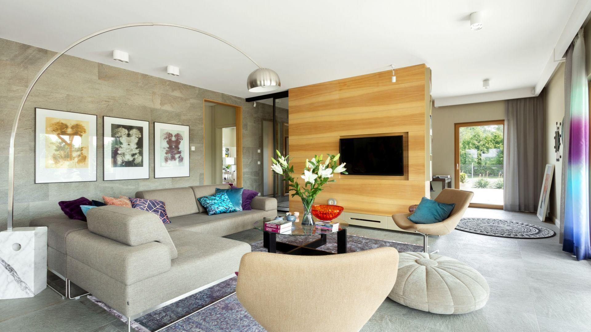 W tym nowoczesnym salonie kolorowe są tylko dodatki: poduszki, dywan, misa na stole. Cała reszta jest spokojna i stonowana. Projekt: Agnieszka Morawiec. Fot. Dekorialove