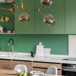 Zielone górne szafki kuchenne w modnym macie zestawiono z naturalnym drewnem dolnej zabudowy. Projekt Finchstudio. Fot. Aleksandra Dermont Ayuko Studio