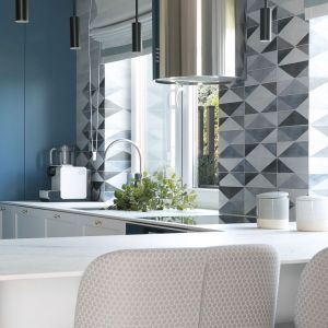 Matowa niebieska zabudowa kuchni skontrastowana z bielą i graficznymi wzorami. Projekt MIKOŁAJSKAstudio. Fot Jakub Dziedzic