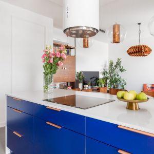 Dolne szafki w kolorze classic blue świetnie komponują się z naturalnym drewnem. Projekt Joanna Rej. Fot. Pion Poziom