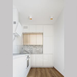 Złote fronty w kuchni doskonale pasuję do jasnej kolorystyki zastosowanej w kuchni. Projekt i zdjęcia: Magdalena Opitek