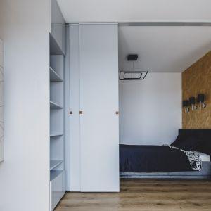 Ze względu na mały metra przestrzeń sypialni od strefy wypoczynku oddziela ruchoma ścianka. Projekt i zdjęcia: Magdalena Opitek