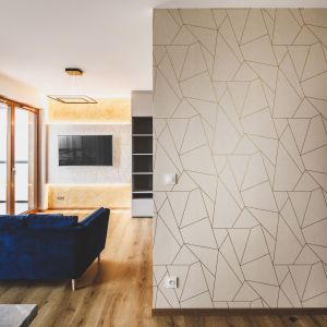 Za ścianą wykończoną tapetę ze złotym wzorem zlokalizowano sypialnię. Projekt i zdjęcia: Magdalena Opitek