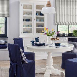 We wnętrzu marynistycznym zadbaj o odpowiednią oprawę stołu – wybierz niebieskie pokrowce na krzesła. Udekoruj okno finezyjną białą firanką i dobierz do niej granatowe zasłony. W ten sposób podkreślisz lekkość i świetlistość wnętrza. Na zdjęciu: poszewka Kinga na poduszkę z kolekcji tkanin Quadro 24 zł (43x43 cm). Fot. Dekoria.pl