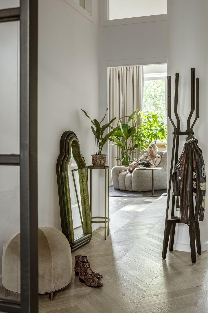Beżowa pufa Stado (Nurt), lustro TRN mirror/triple (Pani Jurek), drewniany wieszak Pilo (Tfory), kwietnik Blossom (The Good Living & Co), rośliny (Plants For Humans), fotel projektu Tomka Rygalika (Nobonobo).