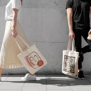 Torby z nadrukiem są wykonane w 100% z bawełny pochodzącej z recyklingu w naturalnym beżowym kolorze.