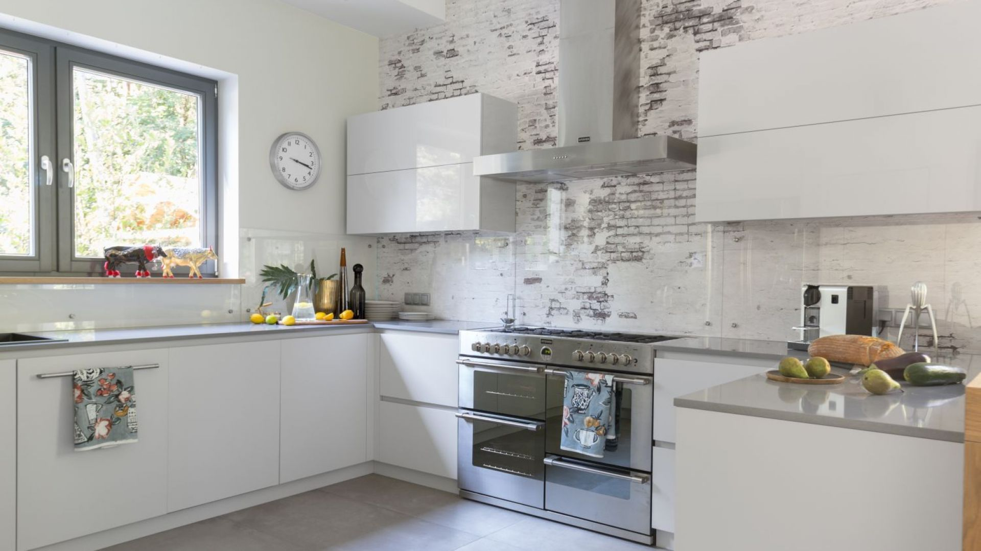 Ścianę nad blatem w kuchni zdobi bardzo subtelna tapeta imitująca cegłę. Zabezpieczą ją przezroczysta, praktycznie niewidoczna tafla szkła. Projekt: Małgorzata Denst. Fot. Pion Poziom