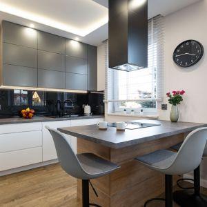 Szkło w czarnym kolorze nadało kuchni elegancji. Doskonale prezentuje się w otoczeniu bieli, drewna i szarości. Projekt: Anna Kamińska, Fuxja Studio Projektowe. Fot. Alla Boroń