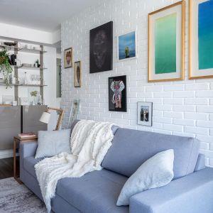 Nad kanapą na ścianie z białej cegły wyeksponowano grafiki i plakaty. Projekt: Momba Arquitetura, Argentyna. Zdjęcia: Guilherme Pucci