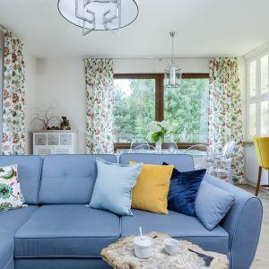 Wzorzyste zasłony (Dekoria) oraz akcenty w postaci niebieskiej kanapy i żółtych krzeseł przy półwyspie pięknie ożywiły przestrzeń. Na podłodze ułożono neutralne, wysokiej klasy panele marki Haro. Projekt: Justyna Mojżyk, poliFORMA. Fot. Monika Filipiuk-Obałek