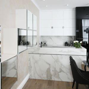 Szklane i lustrzane fronty tworzą ciekawe efekty wizualne w otwartej kuchni, dodając jej przy tym szczyptę galmour. Projekt Karolina Łuczyńska. Fot. Bartosz Jarosz.